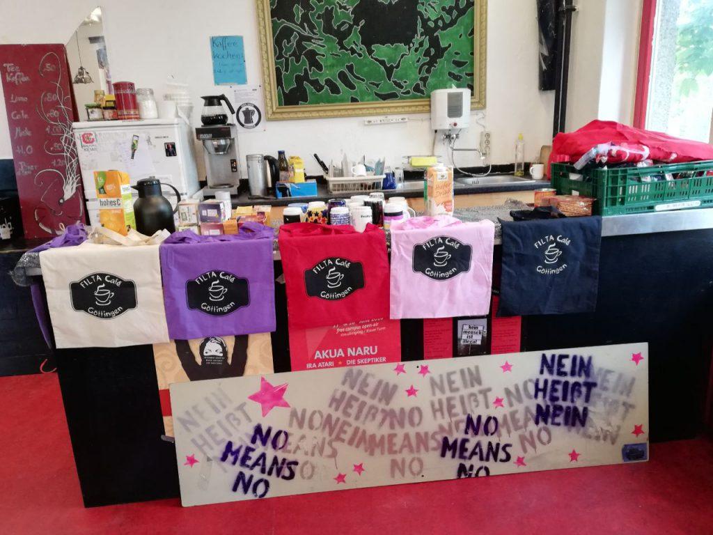 Theke mit Kaffeekannen und Kaffeetassen. Außerdem Beutel mit Siebdruck Logo des Filta Cafés.